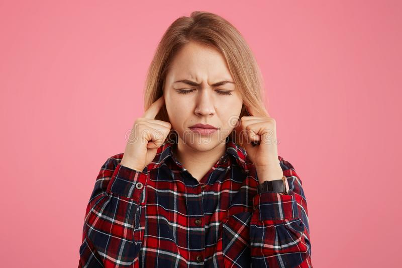 Portrait of beautiful stressful female closes eyes in panic and plugs ears, hears very loud noise, has headache because of it, iso royalty free stock images