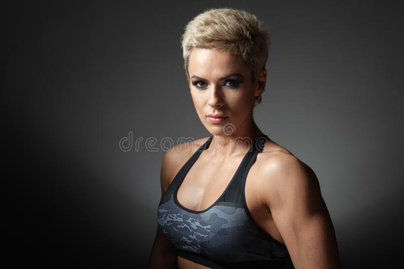 Portrait of a beautiful strong woman with short haircut and make-up. Portrait of a beautiful strong woman in sportswear with a short haircut and make-up. The royalty free stock photo