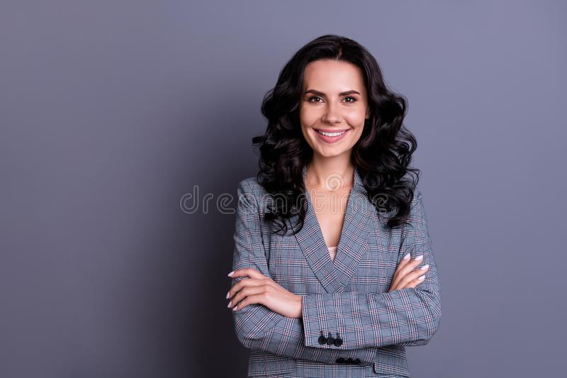 Portrait of beautiful successful freelancer with curly hairstyle crossing her hands wearing blazer isolated over gray stock photography