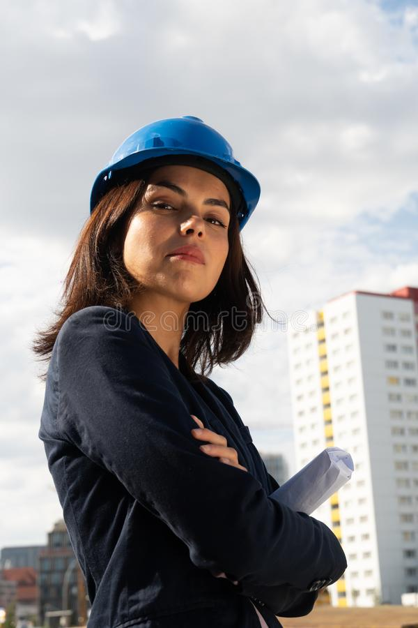 Charming woman architect posing with folded arms. Portrait of a beautiful and successful lady architect wearing a blue safety helmet and posing outdoors with stock image