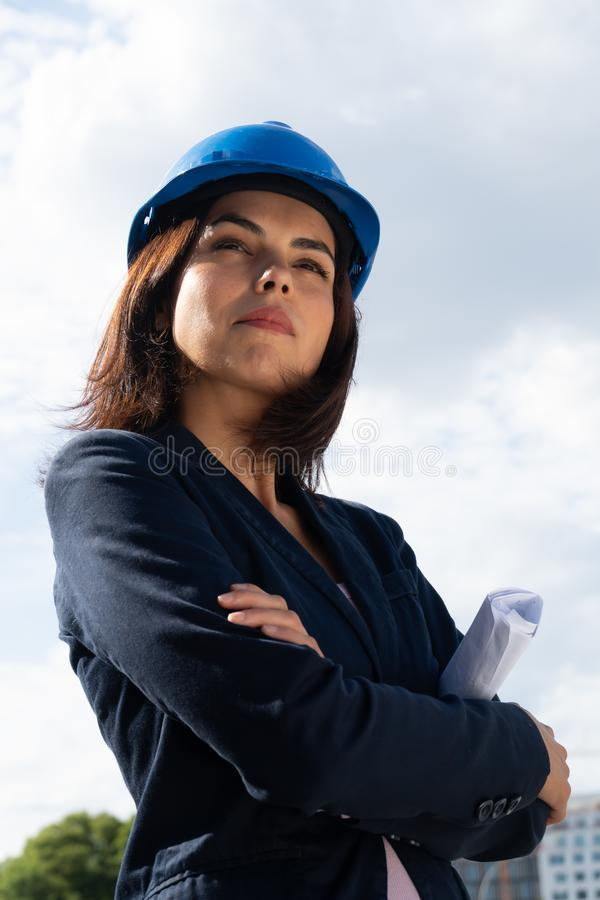 Charming woman architect posing with folded arms. Portrait of a beautiful and successful lady architect wearing a blue safety helmet and posing outdoors with stock photography