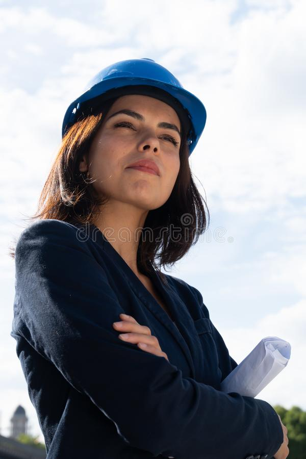 Charming woman architect posing with folded arms. Portrait of a beautiful and successful lady architect wearing a blue safety helmet and posing outdoors with royalty free stock photos