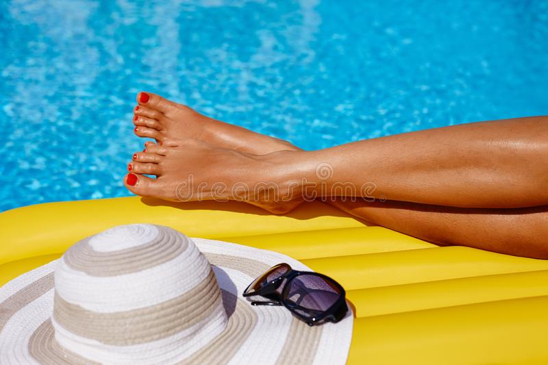 Portrait of beautiful tanned woman relaxing in bikini and hat in swimming pool. Gel polish red manicure. Hot summer day and bright stock photos