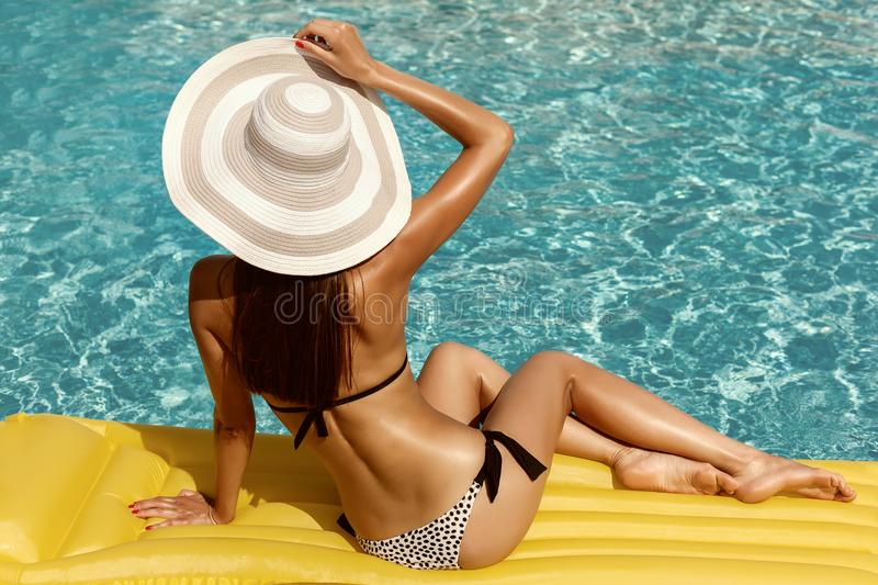 Portrait of beautiful tanned woman relaxing in bikini and hat in swimming pool. Gel polish red manicure. Hot summer day and bright. Sunny light stock photos