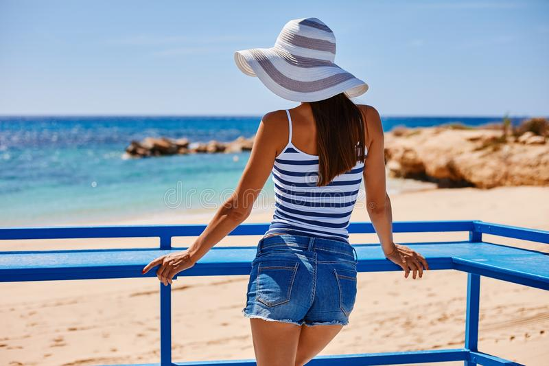 Portrait of beautiful tanned woman at the sea coast in hat and retro style clothes. Hot summer day and bright sunny light. Panoramic view on sea shore near stock photo