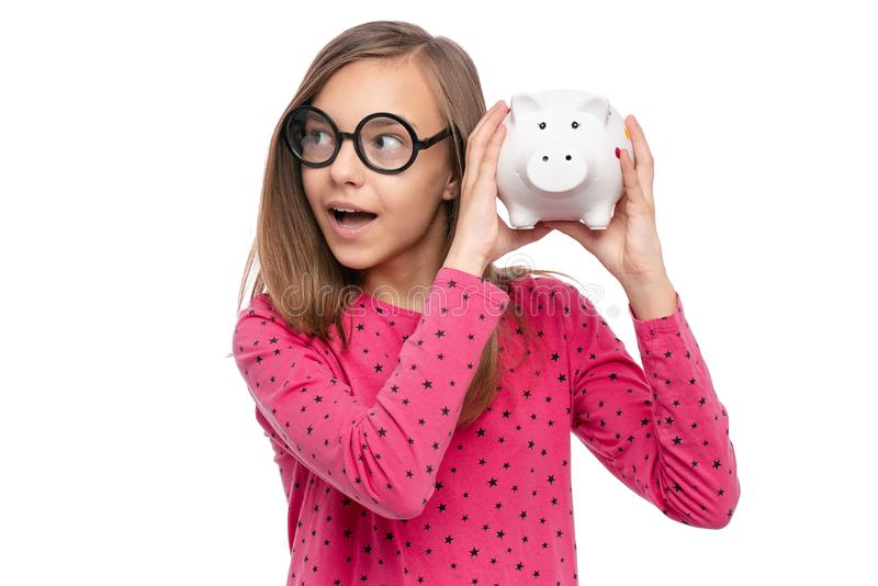 Teen girl with piggy bank. Portrait of beautiful Teen Girl in funny eye Glasses holding Piggy Bank, isolated on white background. Saving Money and childhood stock images