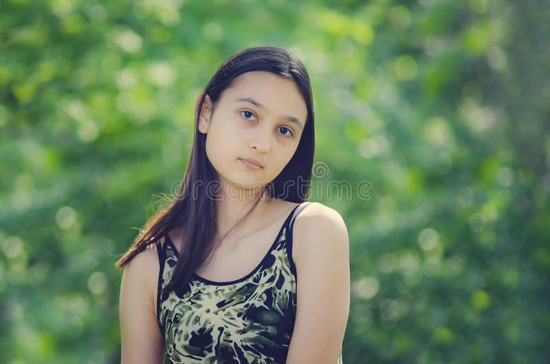 Portrait of a beautiful teenage girl against a background of green foliage stock image