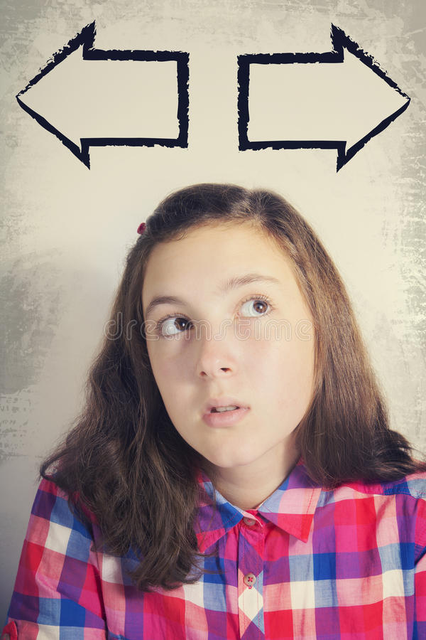 Portrait of beautiful teenage girl in dilemma. Portrait of beautiful teenage girl thinking and looking up thinking and lloking up to two oposite pointing arrows stock photos
