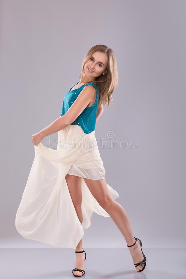 Portrait of beautiful teenage girl in white and blue dress over gray background royalty free stock photography