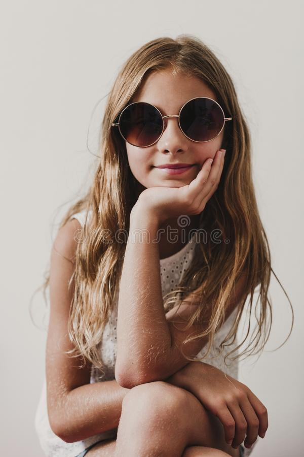 Portrait of beautiful teenager girl at home. Sitting and wearing modern sunglasses. white background. Happiness and lifestyle stock image