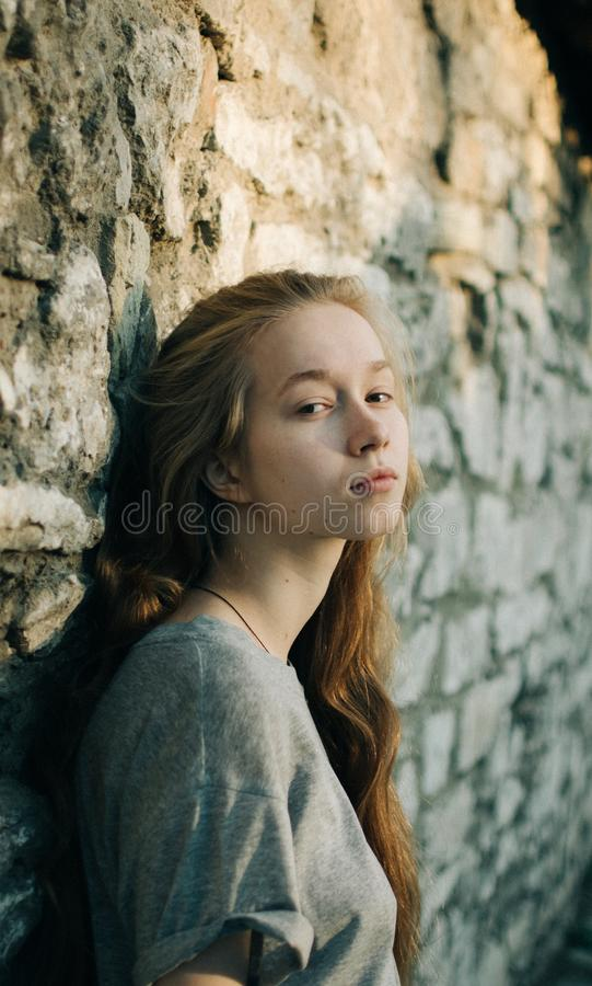Portrait of beautiful teenager girl leaning on textured stone wall outdoors, looking smiling at camera. stock image