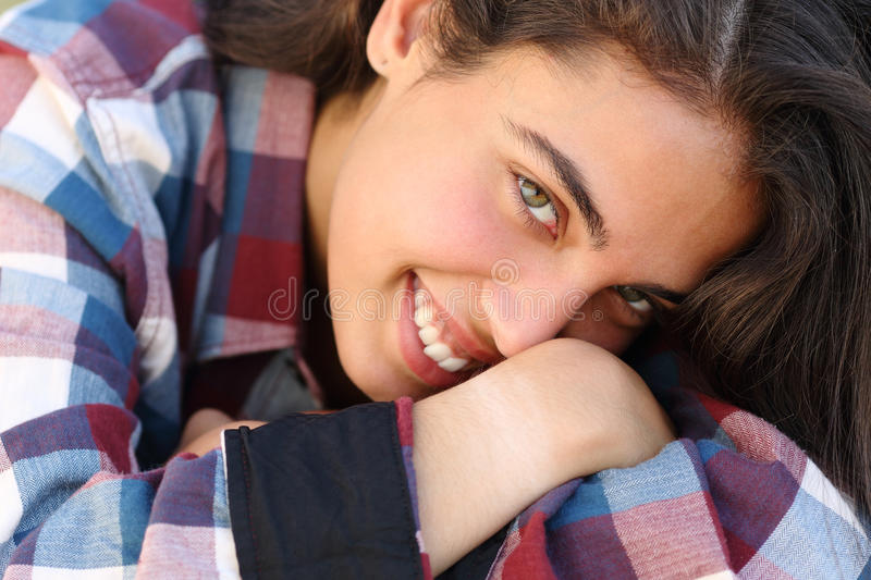 Portrait of a beautiful teenager girl smiling and looking at camera. Very close up portrait of a happy beautiful teenager girl smiling and looking at camera royalty free stock photo