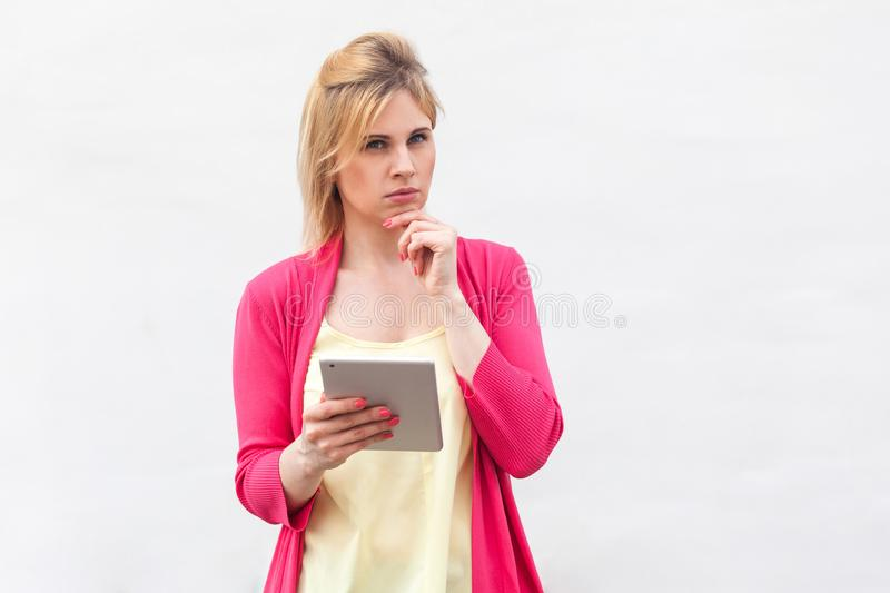 Portrait of beautiful thoughtful businesswoman young woman in pink blouse standing, using tablet to planning her to do list with stock photo