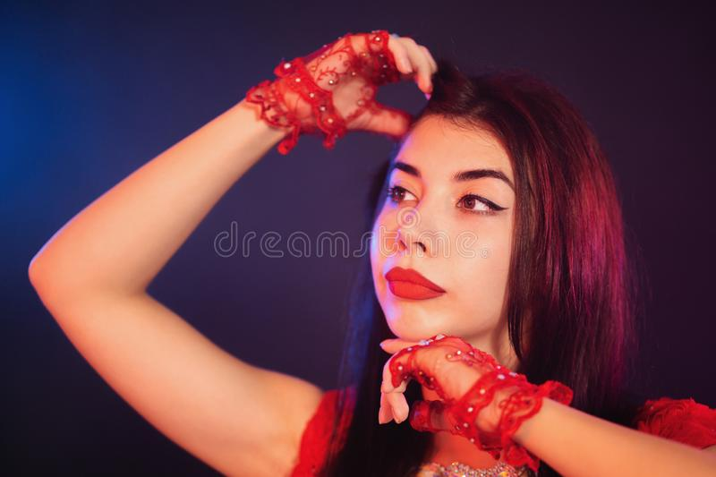 Portrait of beautiful traditional oriental belly dancer girl dancing on blue neon smoky background. Woman in red exotic costu stock image