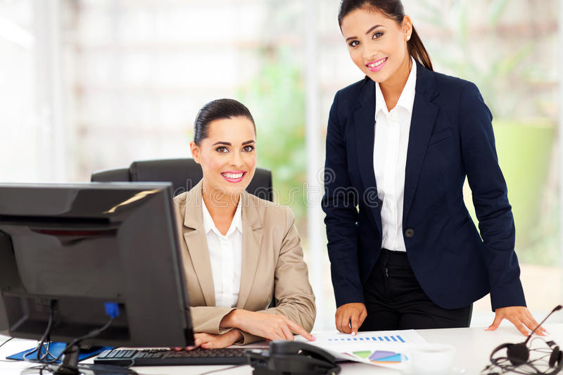 Two business women. Portrait of beautiful two smiling business women in office stock photography