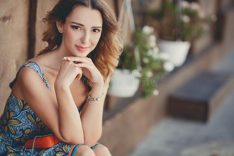 Portrait of a beautiful village woman. Happy woman,beautiful model brunette with long curly hair and brown eyes,a beautiful smile,in a blue summer dress royalty free stock images