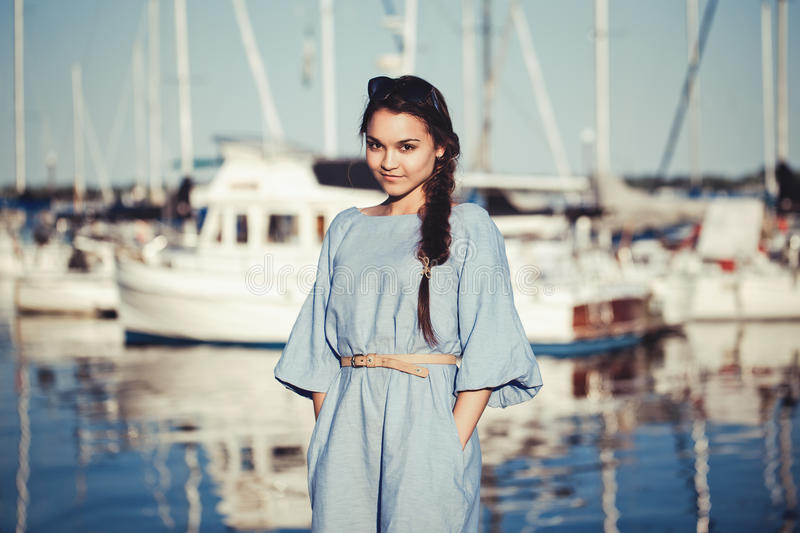 Portrait of beautiful white Caucasian brunette woman with tanned skin in blue dress, by seashore lakeshore stock photography