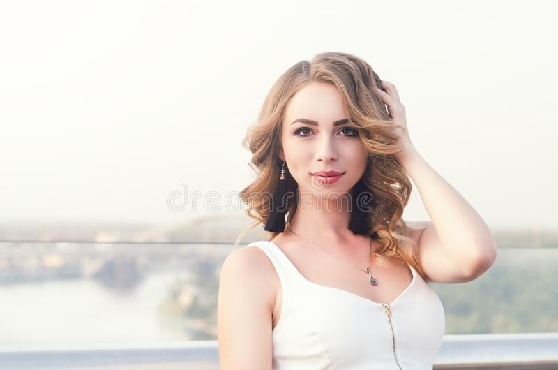 Portrait of beautiful white Caucasian girl woman with long hair outside in city street bridge, looking in camera, lifestyle. Portrait concept stock images