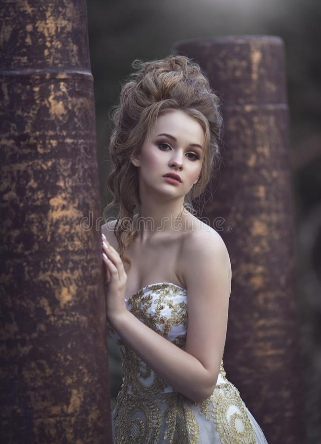 Beautiful woman in an ancient medieval dress, with a high complex historical hairstyle near the walls of the castle. royalty free stock photos