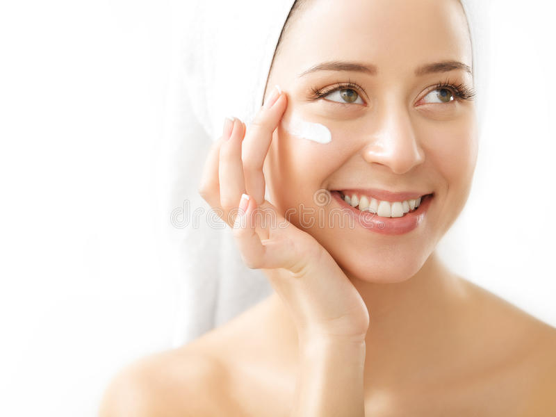 Portrait of beautiful woman applying cream on face - isolated on royalty free stock images