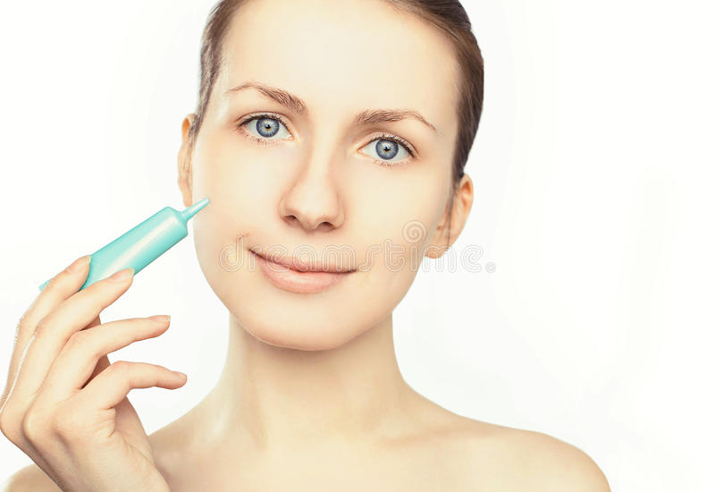 Portrait of beautiful woman applying cream on a white background stock image