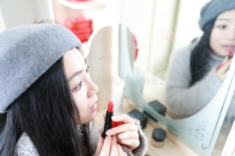 Make-up , Applying lipstick using lip concealer brush. Portrait of beautiful woman applying lipstick using lip concealer brush . A close-up of a lips of a woman royalty free stock photography