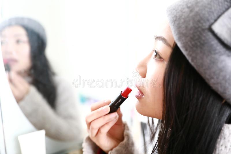 Make-up , Applying lipstick using lip concealer brush. Portrait of beautiful woman applying lipstick using lip concealer brush . A close-up of a lips of a woman stock photography