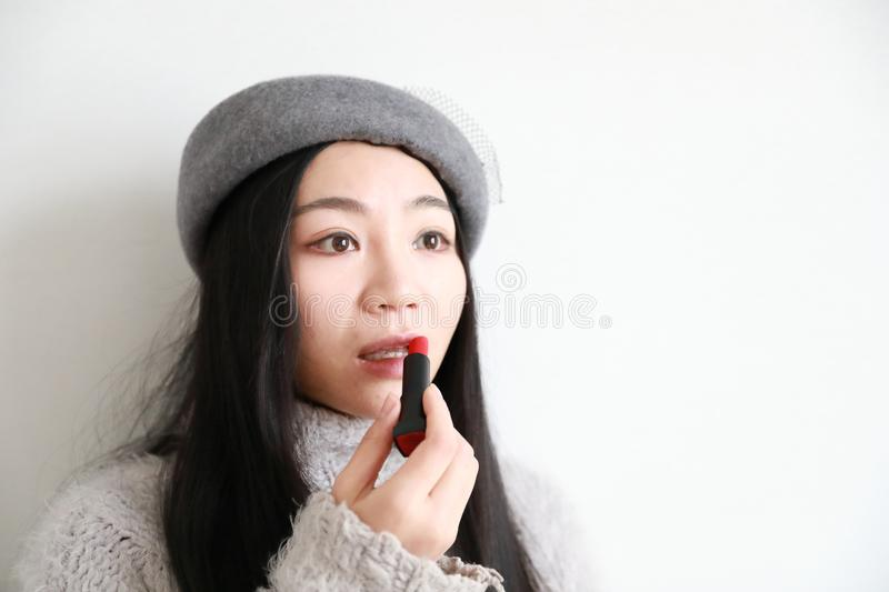 Make-up , Applying lipstick using lip concealer brush. Portrait of beautiful woman applying lipstick using lip concealer brush . A close-up of a lips of a woman stock images