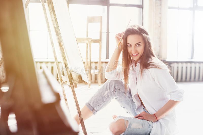 Beautiful woman artist painting on canvas at workspace in sunlight. Portrait of beautiful woman artist painting on canvas at workspace in sunlight royalty free stock photo