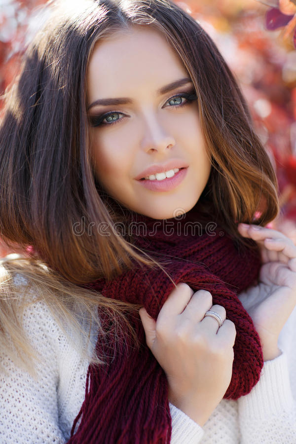 Portrait of beautiful woman in autumn Park. Beautiful young woman in white knitted sweater,round neck wears a maroon knitted scarf,brunette,long straight hair royalty free stock image