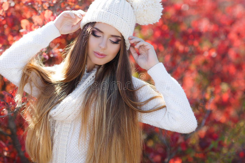 Portrait of beautiful woman in autumn Park. Beautiful young woman in white knitted sweater and white knit cap,brunette,long straight hair,drooping eyelids with royalty free stock images