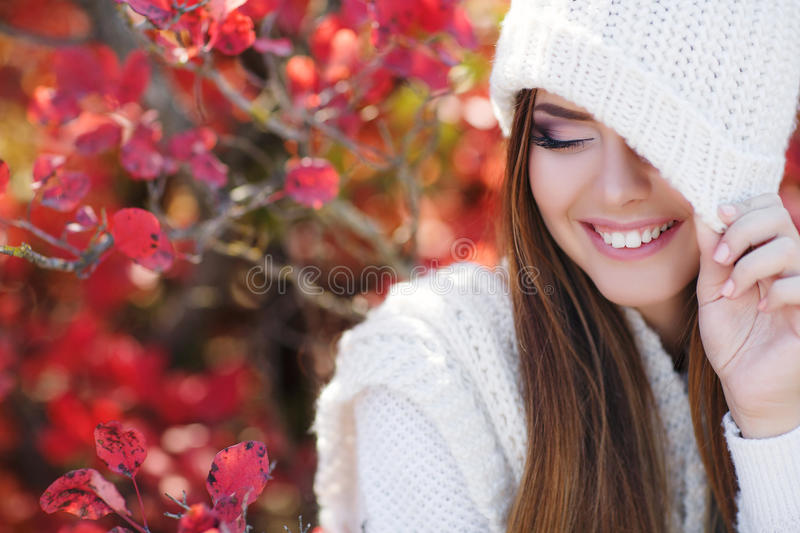 Portrait of beautiful woman in autumn Park. Beautiful young woman in white knitted sweater and white knit cap,brunette,long straight hair,drooping eyelids with royalty free stock photography