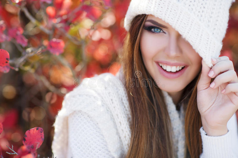 Portrait of beautiful woman in autumn Park. Beautiful young woman in white knitted sweater and white knit cap,brunette,long straight hair,gray eyes,pink lipstick royalty free stock photos