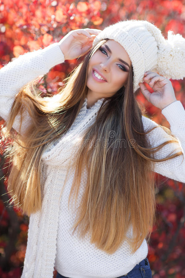 Portrait of beautiful woman in autumn Park. Beautiful young woman in white knitted sweater and white knit cap,brunette,long straight hair,gray eyes,pink lipstick royalty free stock image