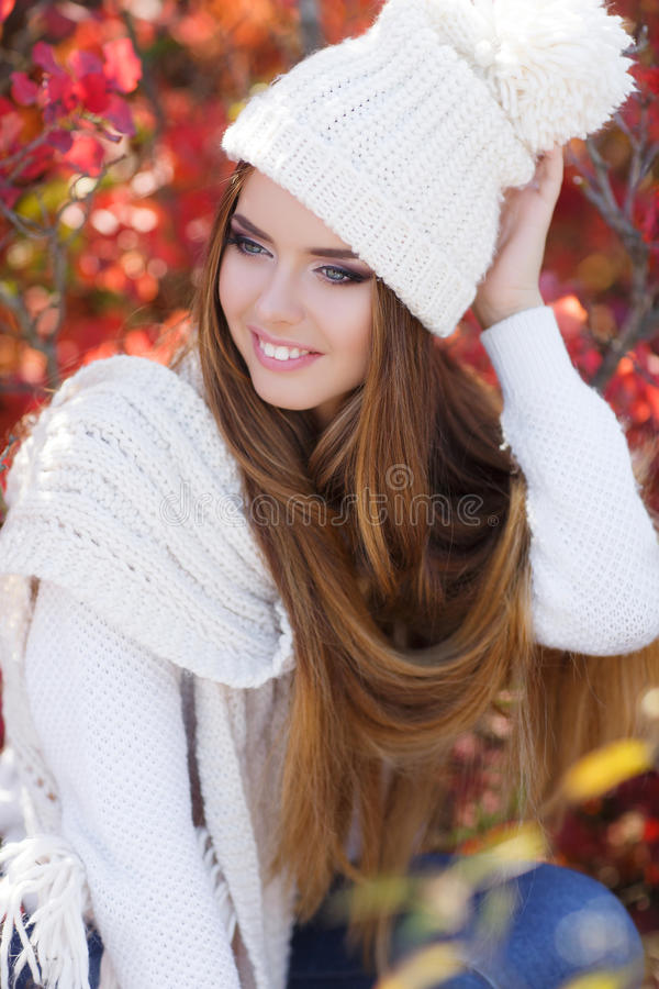 Portrait of beautiful woman in autumn Park. Beautiful young woman in white knitted sweater and white knit cap,brunette,long straight hair,gray eyes,pink lipstick stock images