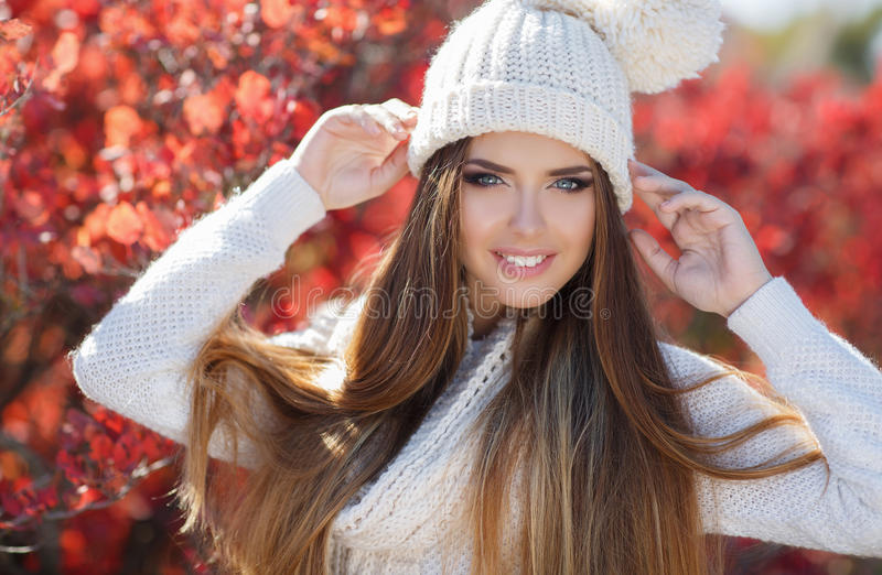 Portrait of beautiful woman in autumn Park. Beautiful young woman in white knitted sweater and white knit cap,brunette,long straight hair,gray eyes,pink lipstick stock photography