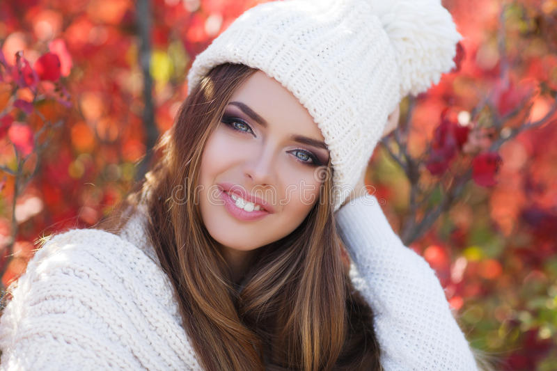 Portrait of beautiful woman in autumn Park. Beautiful young woman in white knitted sweater and white knit cap,brunette,long straight hair,gray eyes,pink lipstick stock image