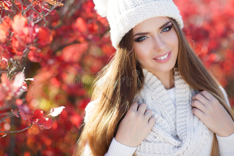 Portrait of beautiful woman in autumn Park. Beautiful young woman in white knitted sweater and white knit cap,brunette,long straight hair,gray eyes,pink lipstick royalty free stock photography