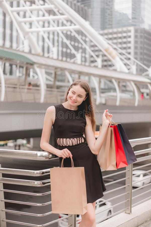 Portrait of beautiful woman in black dress holding shopping bags at mall,Lifestyle concept royalty free stock images