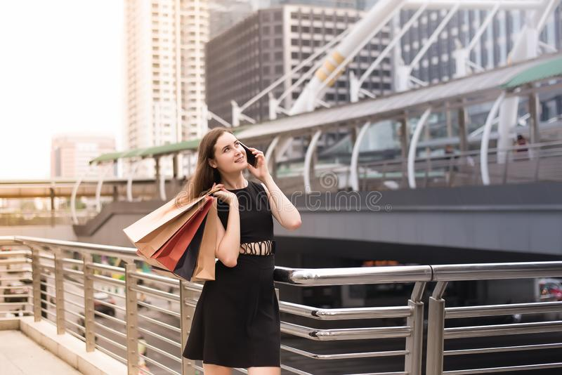 Portrait of beautiful woman in black dress using cellphone and holding shopping bags at mall,Lifestyle concept stock photos