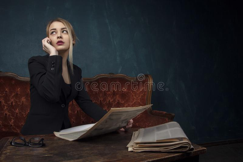 Portrait of a beautiful woman in a black suit reading a newspaper and talking on the phone in an expensive antique interior agains. T a blue textured wall with stock photography