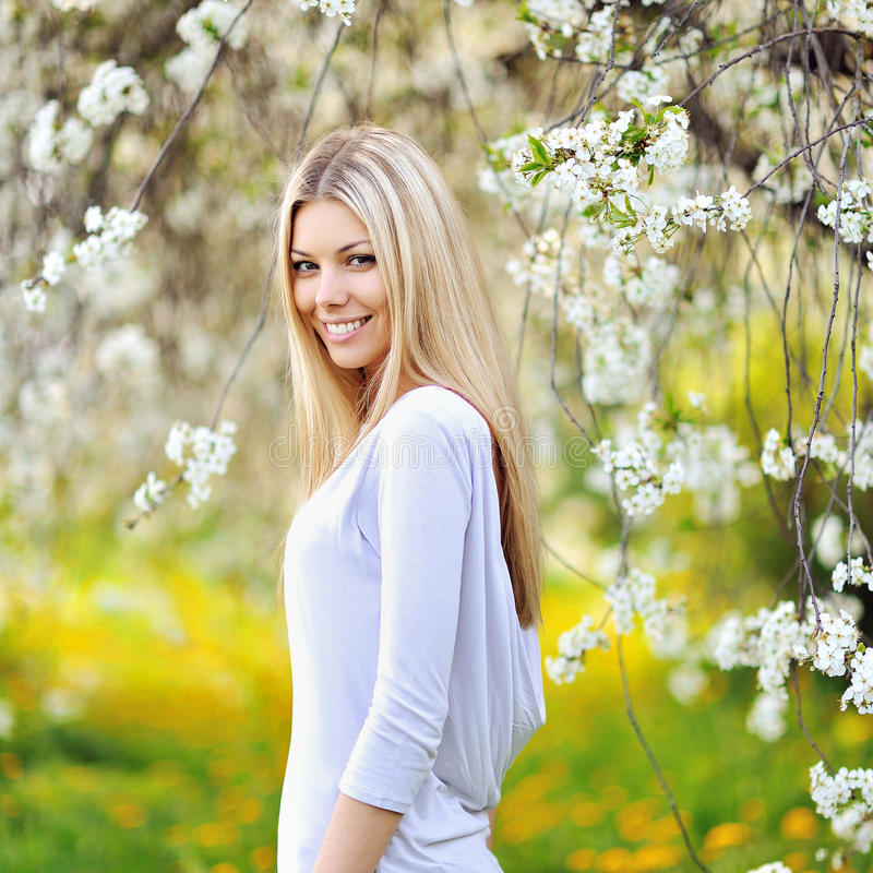 Portrait of a beautiful woman in blooming park in spring royalty free stock photography