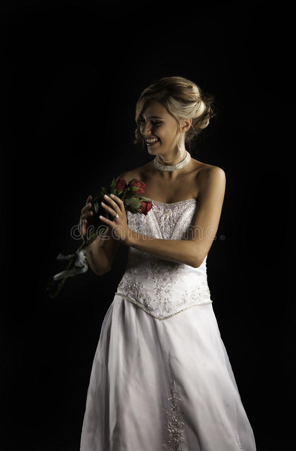 Portrait of beautiful woman in bridal clothes catching a bouquet of red roses.