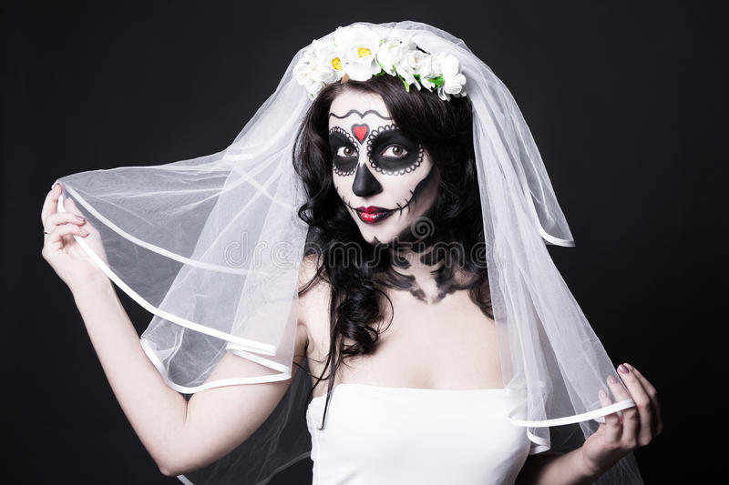 Portrait of beautiful woman bride with creative sugar skull make. Up and bridal veil over black background royalty free stock photography