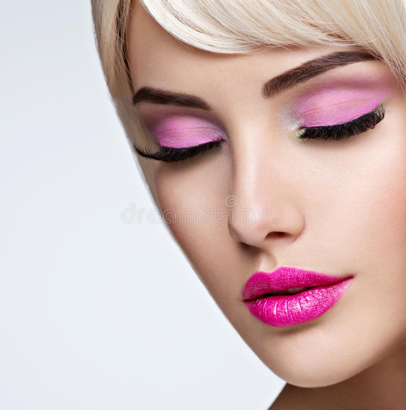 Portrait of  a  Beautiful  woman with  bright pink make-up. Face of a Fashion model with pink lipstick. Pretty girl posing at studio royalty free stock image