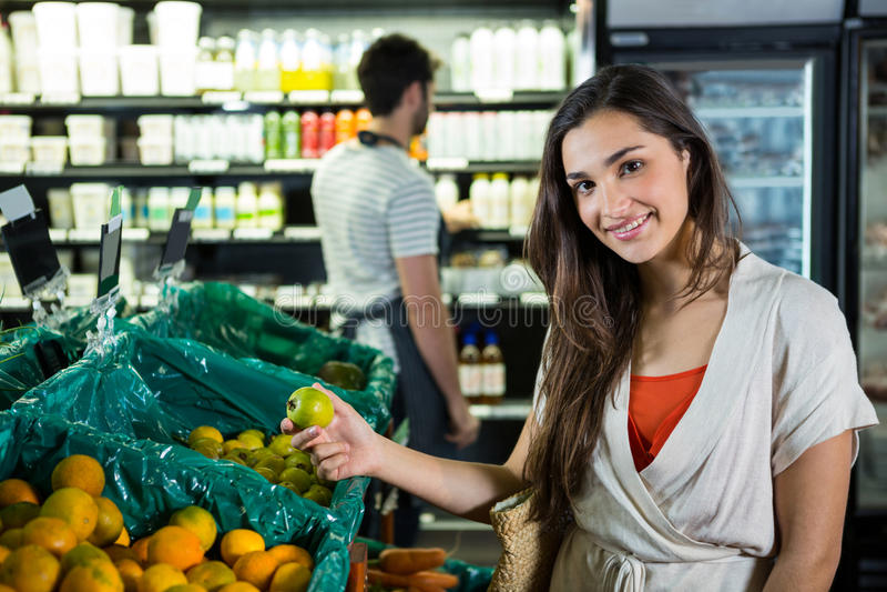 Portrait of beautiful woman buying fruit in organic section. Portrait of beautiful women buying fruit in organic section of supermarket stock photo