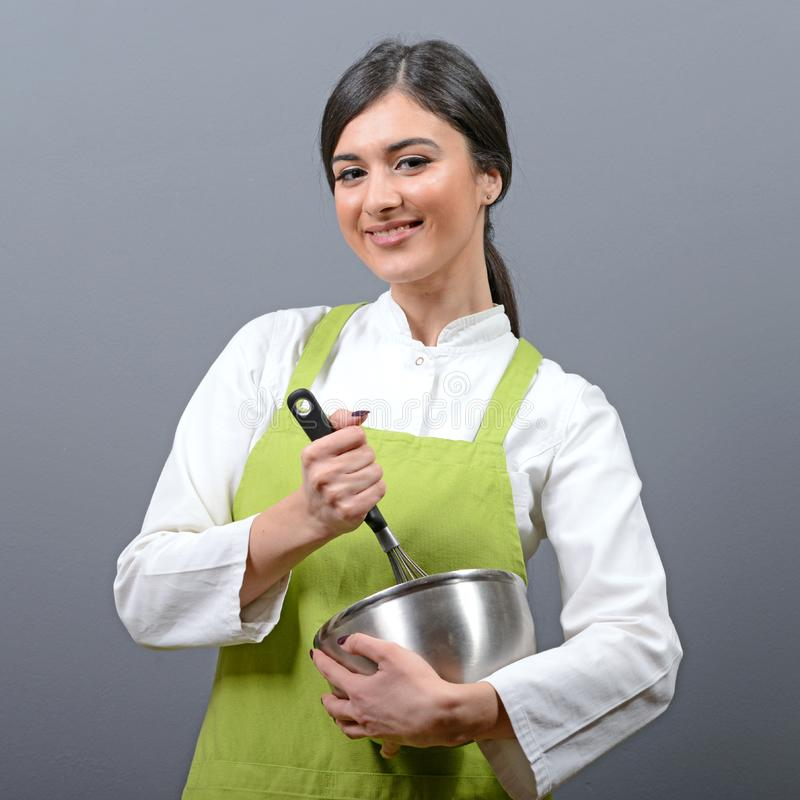 Portrait of beautiful woman chef mixing in a bowl against gray background royalty free stock image