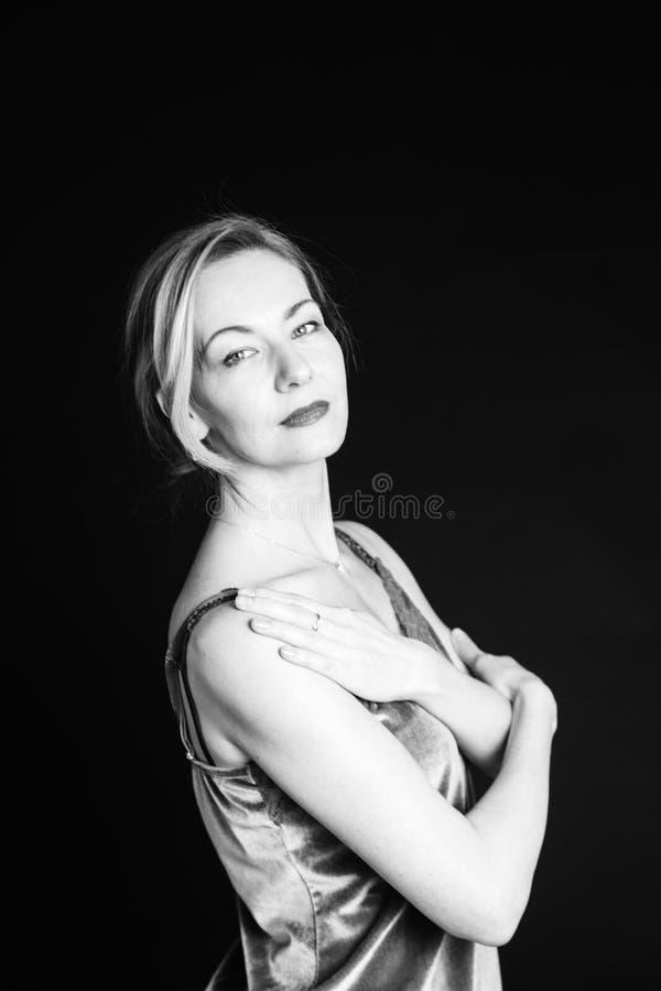 Portrait of a beautiful woman. Close up studio portrait of beautiful woman in a silk dress against black background stock photos