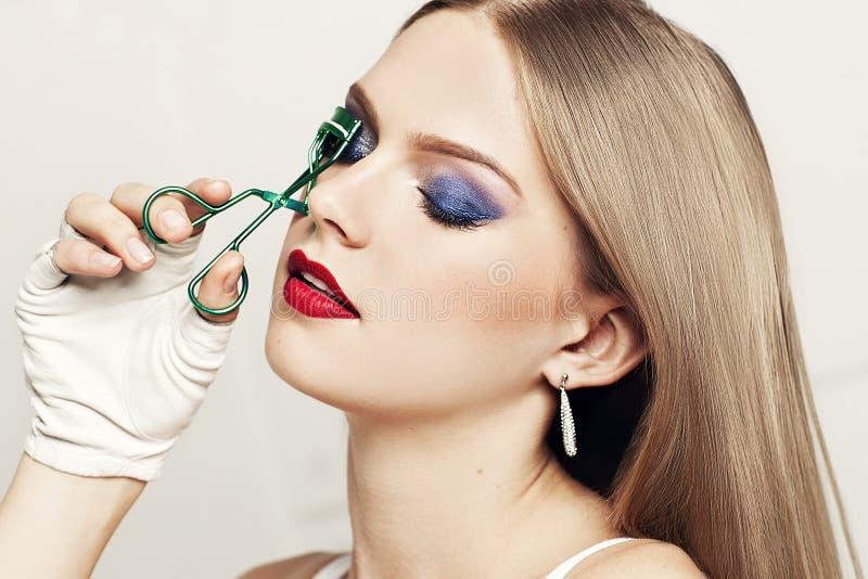 Portrait of beautiful woman with closed eyes holding eyelash curler royalty free stock image