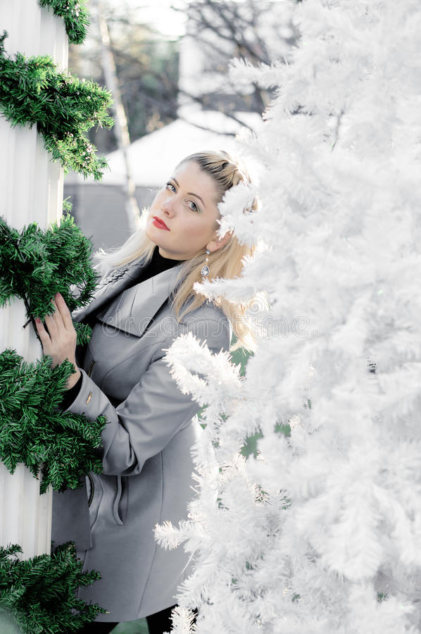 Portrait of the beautiful woman between the column braided by fir-tree branches and a New Year tree. A subject the woman and holidays Christmas and New Year stock photo